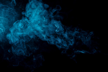 Abstract art colored  blue smoke on black isolated background. Stop the movement of multicolored smoke on dark background Stock Photo