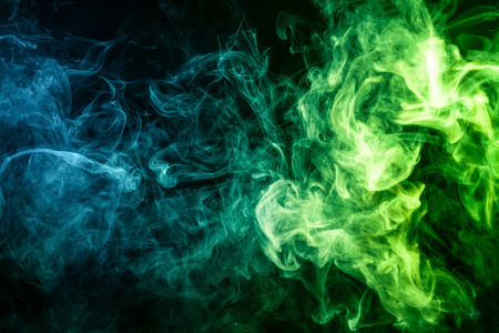 Thick blue and green smoke on a black isolated background. Background from the smoke of vape