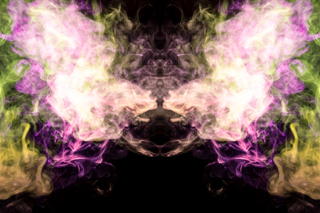 Thick colorful smoke of green pink in the form of a skull, monster, dragon on a black isolated background. Background from the smoke of vape. Mocap for cool t-shirts Stock Photo