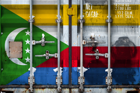 Close-up of the container with the national flag of Comoros. The concept of Comoros export-import and national delivery of goods.