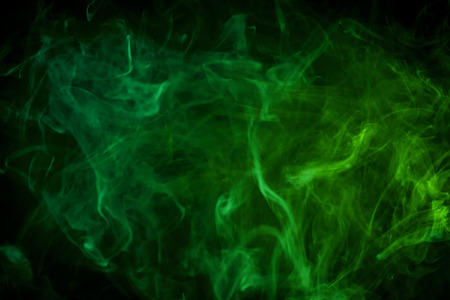 Cloud of green smoke on a black isolated background. Background from the smoke of vape