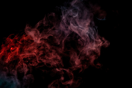 Abstract art  red and blue colored smoke on black isolated background. Stop the movement of multicolored smoke on dark background