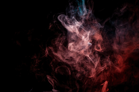 Frozen abstract movement of  explosion smoke multiple colors  red and blue on black background. Background from the smoke of vape Foto de archivo