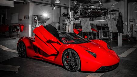 Novosibirsk, Russia - August 16, 2018: Sports car red  Marussia model B1  in a car salon: the doors are raised up Standard-Bild - 133071926