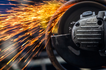 A young man welder in a white gloves grinder metal an angle grinder   in the   workshop, sparks fly to the side. The concept of car repair and car repair shop Imagens
