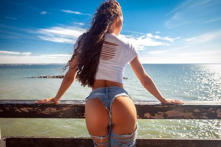 concetto di estate. Viaggio di vacanza. Culo e fianchi ideali della donna: perfetto programma di terapia anticellulite e di cura della pelle. Foto della spiaggia dell'oceano.