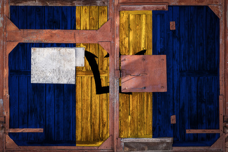 Close-up of old warehouse gate with national flag of Barbados. The concept of export-import Barbados, storage of goods and national delivery of goods. Flag in grunge style