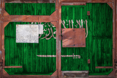 Close-up of old warehouse gate with national flag of Saudi Arabia. The concept of export-import Saudi Arabia, storage of goods and national delivery of goods. Flag in grunge style 免版税图像