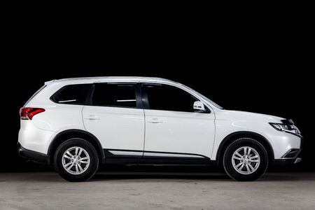 Novosibirsk, Russia - March 10, 2019:  Mitsubishi Outlander, side view. Photography of a modern car  on a parking in Novosibirsk against a black wall Standard-Bild - 133071980