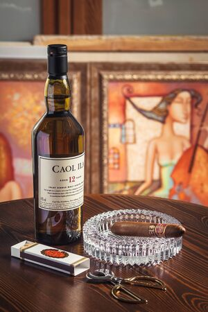 Novosibirsk, Russia - April 07, 2017:  Caol ila Single Malt Whisky,cigar, ashtray and scissors for cigars   at the bar wooden counter Standard-Bild - 133072000
