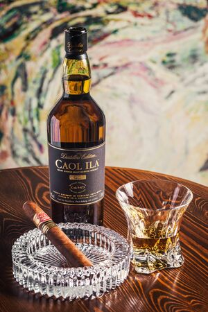 Novosibirsk, Russia - April 07, 2017:  Caol ila Single Malt Whisky,cigar, ashtray and a glass of whiskey   at the bar wooden counter Standard-Bild - 133072001
