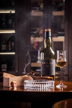 Novosibirsk, Russia - April 07, 2017:  Caol ila Single Malt Whisky,lit cigar and a glass of whiskey   at the bar wooden counter Standard-Bild - 133072002