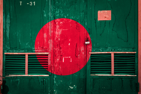 Close-up of old warehouse gate with national flag of Bangladesh. Concept of Bangladesh export-import, storage of goods and national delivery of goods. Flag in grunge style
