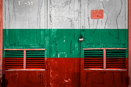 Close-up of old warehouse gate with national flag of Bulgaria. Concept of Bulgaria export-import, storage of goods and national delivery of goods. Flag in grunge style