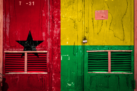 Close-up of old warehouse gate with national flag of Guinea bissau .  Concept of Guinea bissau export-import, storage of goods and national delivery of goods. Flag in grunge style