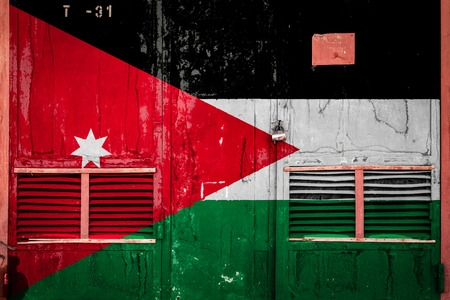 Close-up of old warehouse gate with national flag of Jordan. Concept of Jordan export-import, storage of goods and national delivery of goods. Flag in grunge style