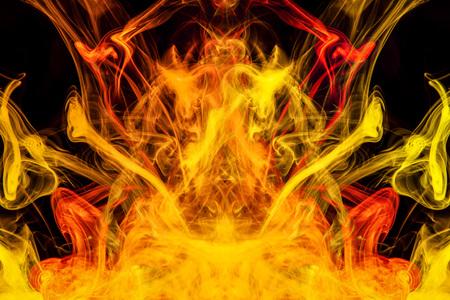 Fumée multicolore dense de couleurs jaunes et oranges sous la forme d'un crâne, monstre, dragon sur fond noir isolé. Fond de vape fumée. Mocap pour t-shirts cool Banque d'images