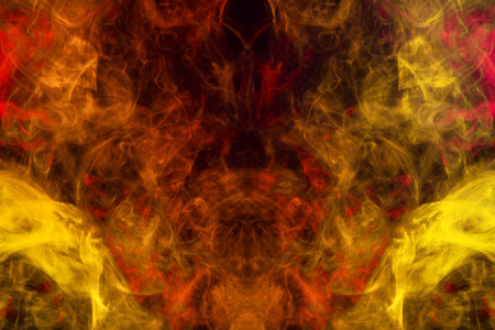 Dense multicolored smoke of   yellow and orange colors in the form of a skull, monster, dragon on a black isolated background. Background of smoke vape. Mocap for cool t-shirts