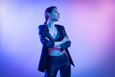Fashion portrait of young elegant girl in jacket. Colored background, studio shot. Beautiful brunette woman posing. hipster girl in neon. Stok Fotoğraf