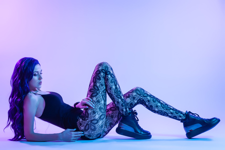 Fashion portrait of young elegant girl in in fishnet tights and underwear . Colored background, studio shot. Beautiful brunette woman posing. hipster girl in neon.