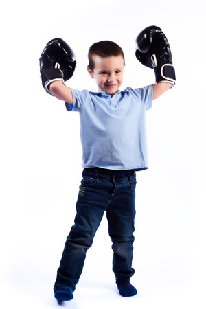 A little boy with dark hair in blue jeans, a blue polo shirt in black and white boxing gloves is having fun, showing biceps and considering himself a winner on a white isolated background in a photo studio Stock fotó