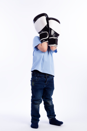 Little boy with dark hair in blue jeans, blue polo t-shirt in black and white boxing gloves is having fun, hiding from a punch on a white isolated background in a photo studio
