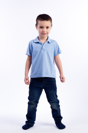 Little smiling boy with dark hair in blue jeans, blue polo t-shirt posing, laughing happily on a white isolated background in a photo studio. Portrait of happy joyful beautiful boy 스톡 콘텐츠