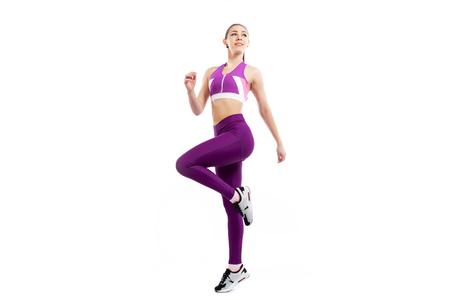 Een donkerharige vrouwencoach in een sportieve roze korte top en gymlegging die oefeningen doet om de benen op te warmen, afwisselend knieflexie op een witte geïsoleerde achtergrond in de studio Stockfoto