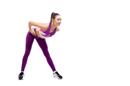 A dark-haired woman coach in a sporty pink short top and gym leggings shows the correct technique of tilting forward for inflating the buttocks on a  white isolated background in studio 写真素材 - 119995696