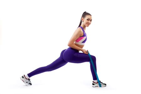 A dark-haired woman coach in a sporty purple short top and gym leggings makes lunges with sport fitness rubber bands on a white isolated background in studio