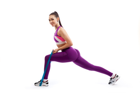 A dark-haired woman coach in a sporty purple short top and gym leggings makes lunges with sport fitness rubber bands on a white isolated background in studio Stock Photo