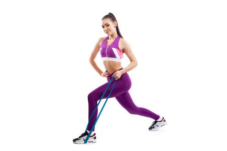 Una entrenadora de cabello oscuro con un top corto de color púrpura deportivo y mallas de gimnasia hace estocadas con bandas de goma de fitness deportivo sobre un fondo blanco aislado en estudio