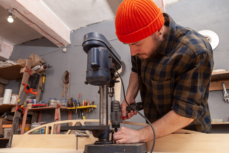 Close up of experienced carpenter in work clothes and small buiness owner  is carving a wooden board on an  modern  hand drill in a light workshop side view, in the background a lot of tools