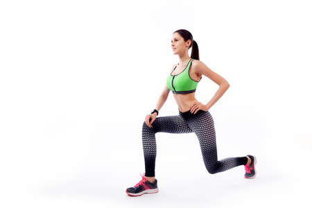 A dark-haired woman coach in a sporty short top and gym leggings makes lunges by the feet forward, hands are held out to the side on a white isolated background in studio