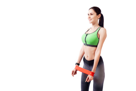 A young woman model in a sporty clothes doing sport exercise on biceps with sport fitness rubber bands on a white isolated background in studio