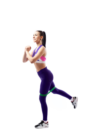 Sporty woman does exercises on legs with sport fitness rubber bands on white background. Photo of muscular woman in sportswear on white background. Strength and motivation.