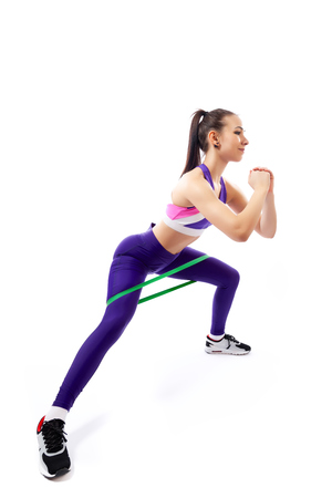 Sporty woman does exercises on legs, makes lunges with sport fitness rubber bands on white background. Photo of muscular woman in sportswear on white background. Strength and motivation.