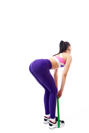 Sporty woman does exercises and stretch on legs and buttons with sport fitness rubber bands on white background. Photo of muscular woman in sportswear on white background. Strength and motivation.