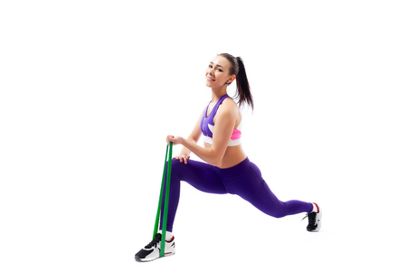 Beautiful young  woman doing lunge exercisewith sport fitness rubber bands  in fitness gym isolated over white background. Fit girl living an active lifestyle 写真素材 - 120792418
