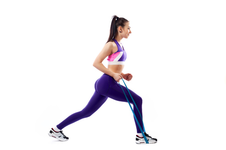 Sporty woman does  exercises on legs, makes lunges  with sport fitness rubber bands  on white background. Photo of muscular woman in sportswear on white background. Strength and motivation. 写真素材 - 120792425