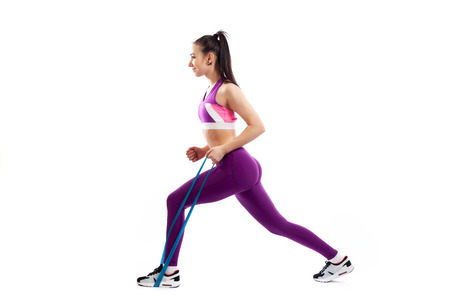 Sporty woman does exercises on legs, makes lunges with sport fitness rubber bands on white background. Photo of muscular woman in sportswear on white background. Strength and motivation. Stock Photo