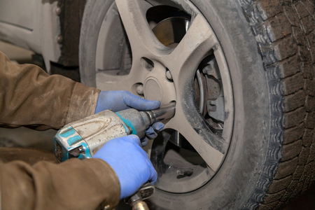 Close up Professional car mechanic changing car wheel in auto repair service. Autoworker doing tire or wheel replacement in garage of repair service station