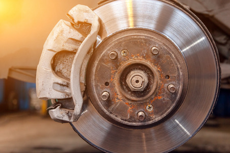 Close-up of heavily worn rear drum brakes on a car raised on a lift in a car repair shop