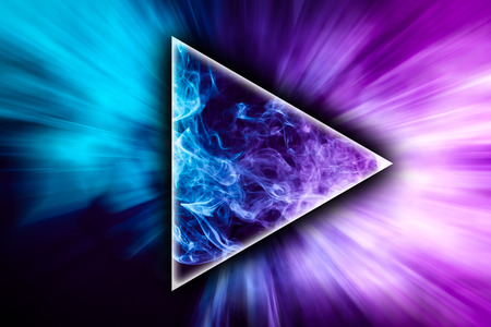 Abstract art colored smoke in the shape of a triangle on black isolated background. Stop the movement of multicolored smoke on dark background