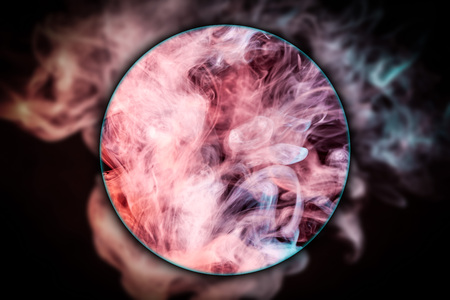 Close-up blue and red bomb smoke blown under a magnifying glass on black isolated background