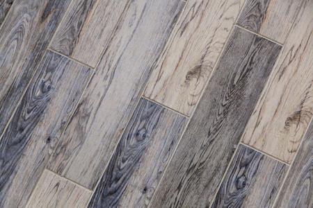 Moderner Vinylboden mit Altholzimitat. Nahaufnahme des neuen grauen Bodenbelags mit Textur aus Fliesen mit braunen Körnern und Knoten. Dekorativer Hintergrund von Holzbrettern. Standard-Bild