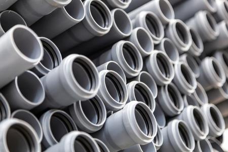 Nahaufnahme graue Sanitär-Kunststoffrohre. Hintergrund von bunten großen Plastikrohren, die auf der Baustelle verwendet werden.
