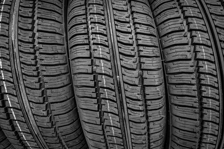 Car tires in a row on a shelf tire. Protector of automobile tires. A number of automobile tires. Close up view on auto mobile new wheel tire surface.