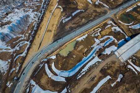 Helicopter drone shot. Aerial photography of a modern roads with car, track in winter, on background forest, construction site, no people 免版税图像