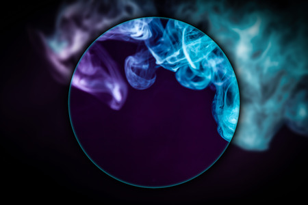 Close-up  swirling  сloud of pink and blue smoke  blown under a magnifying glass on black isolated background